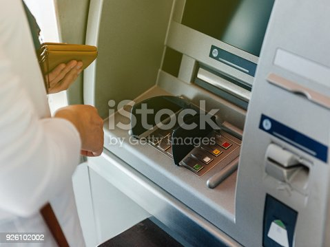 istock Side view of woman using ATM holding wallet an pressing the PIN 926102002