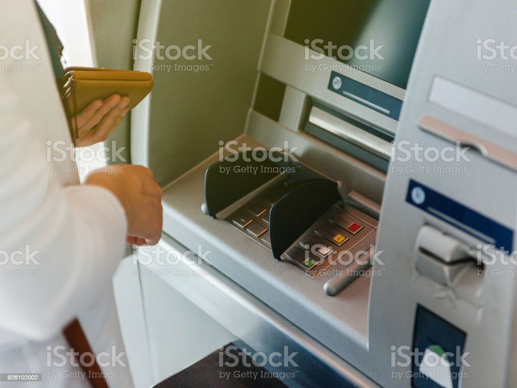 Side view of woman using ATM holding wallet an pressing the PIN stock photo