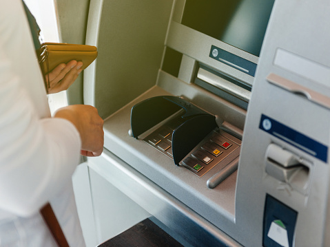 Side View Of Woman Using Atm Holding Wallet An Pressing The Pin Stock Photo - Download Image Now