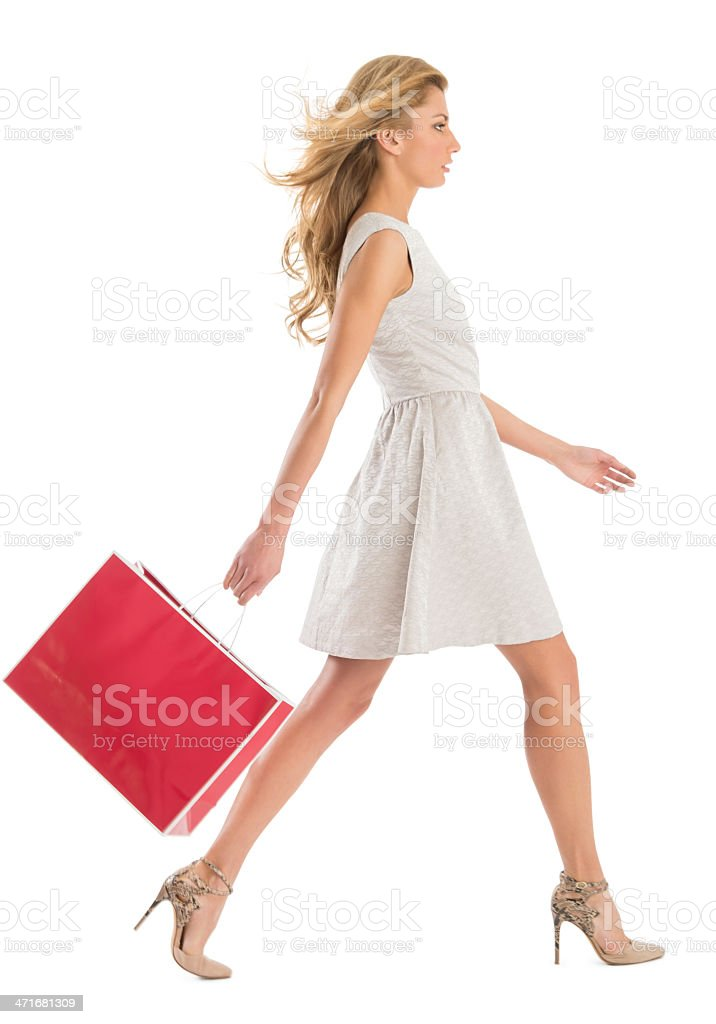 Side View Of Woman Walking With Shopping Bag stock photo