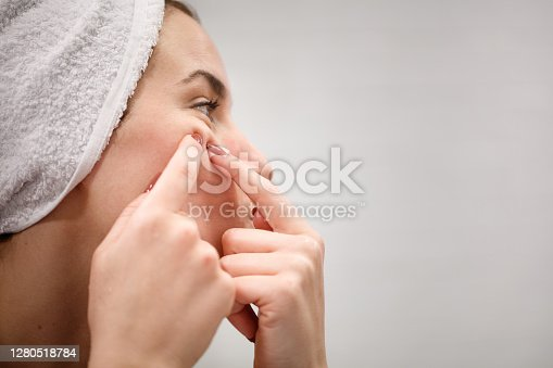 Side view of woman in bathroom mirror wearing towel on hair after shower, squeezing blackead on her cheek with index fingernails