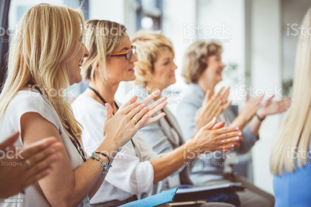 Side view of women clapping hands during seminar Group of businesswomen clapping hands during seminar. Side view. Achievement Stock Photo