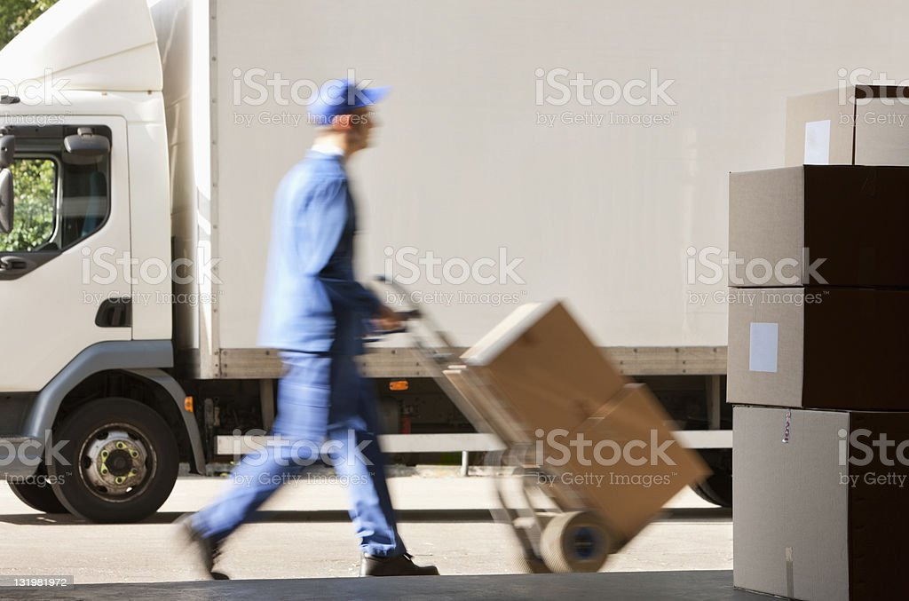 Side view of worker with push cart outside warehouse stock photo
