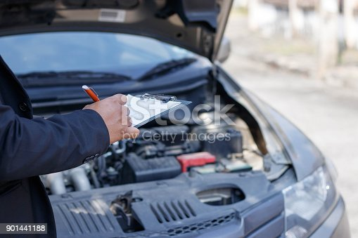 istock Side view of writing on clipboard while insurance agent examining car 901441188