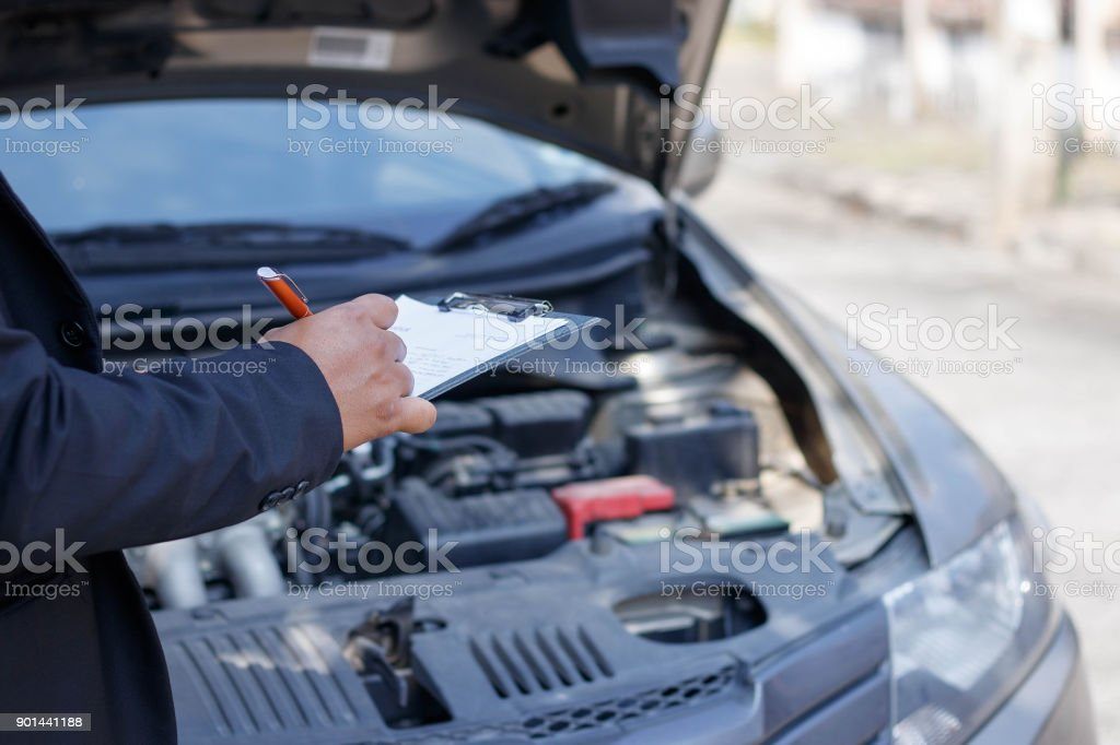 Side view of writing on clipboard while insurance agent examining car stock photo
