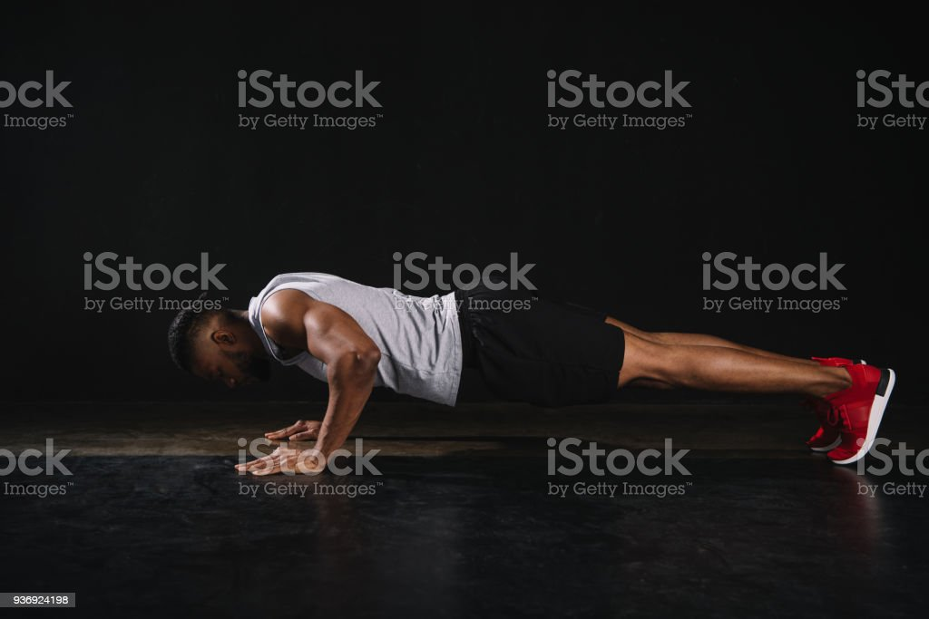 side view of young african american sportsman doing push-ups on black stock photo