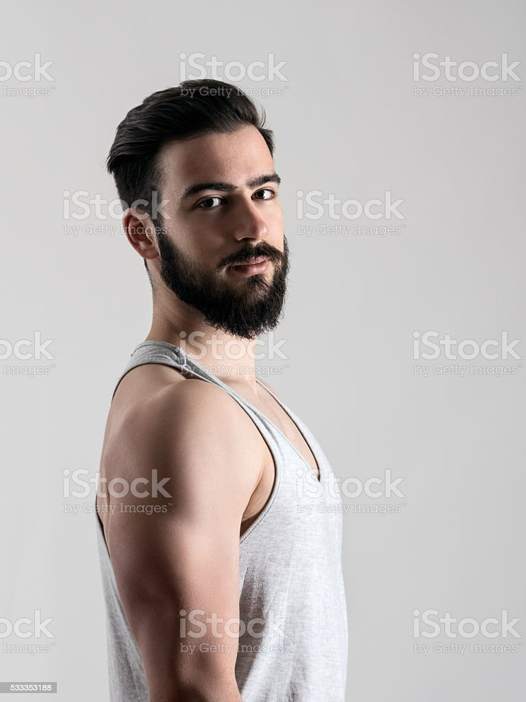 Side view of young athlete in undershirt looking at camera. stock photo
