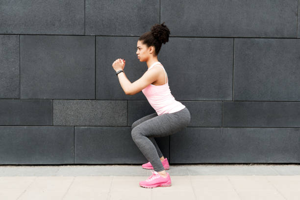 Side view of young athlete squatting at wall stock photo