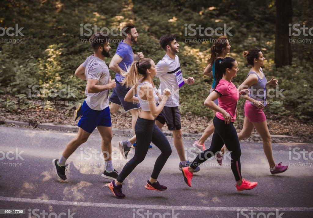 실제로로에서 마라톤을 실행 하는 젊은 선수의 측면 보기. - 로열티 프리 거리 스톡 사진