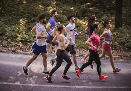 실제로로에서 마라톤을 실행 하는 젊은 선수의 측면 보기 거리에 대한 스톡 사진 및 기타 이미지