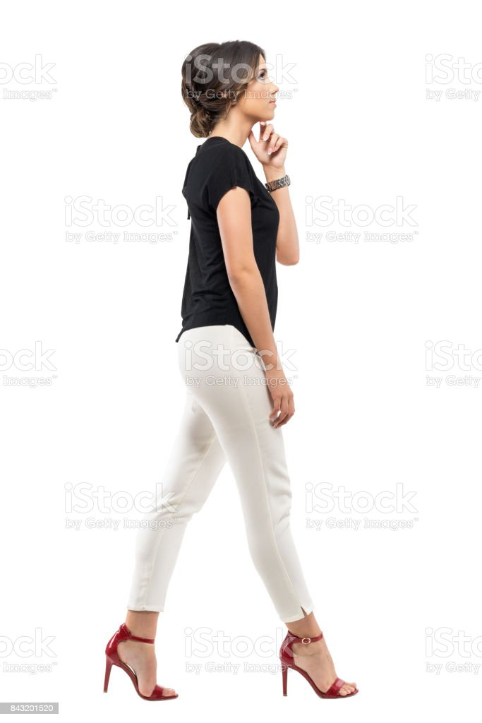 Side view of young business woman in suit thinking and walking looking ahead. stock photo