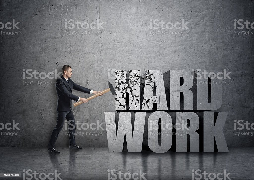Side view of young businessman crashing 3D concrete 'hard work stock photo