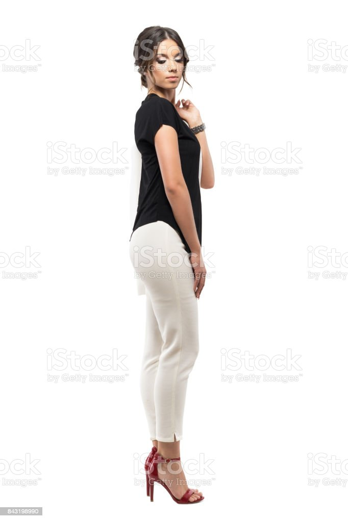 Side view of young businesswoman in suit carrying jacket and looking down over the shoulder. stock photo