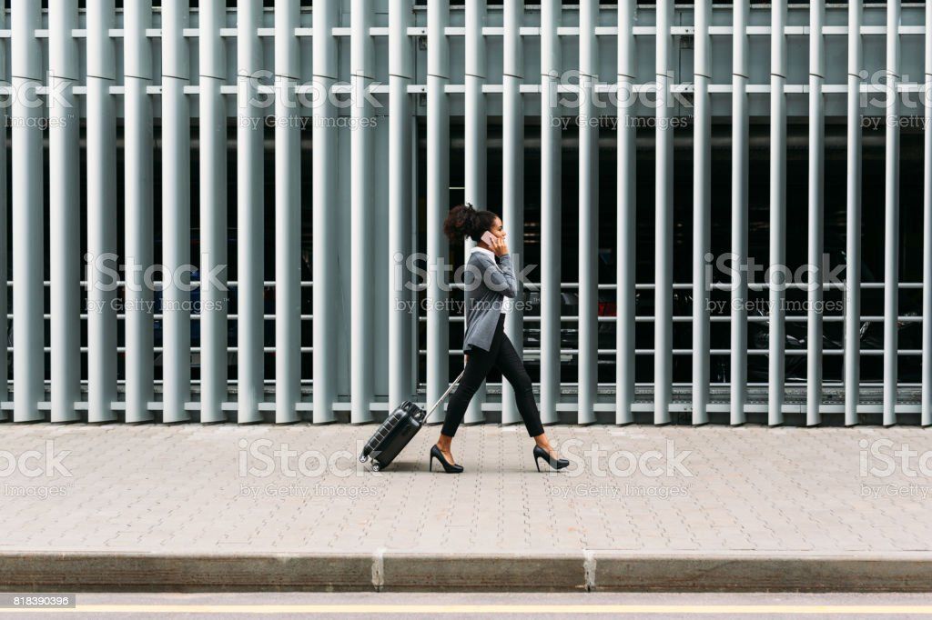 Side view of young businesswoman walking with suitcase stock photo