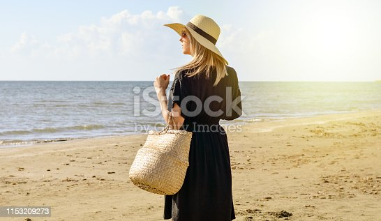 Side view of young  caucasian woman with black dress  ,  straw hat and basket waliking  on beach   and relaxing . Bright warm filter .