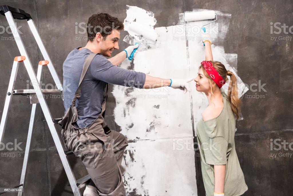Seitenansicht des jungen Paares Malerei Wand zusammen, Renovierung Wohnkonzept Lizenzfreies stock-foto