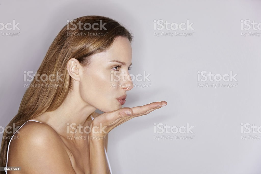 Side View Of Young Female Blowing A Kiss At Copyspace Stock