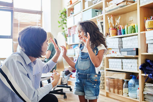 istock Side view of young female teacher giving high five to adorable girl during art class in school 1143087335