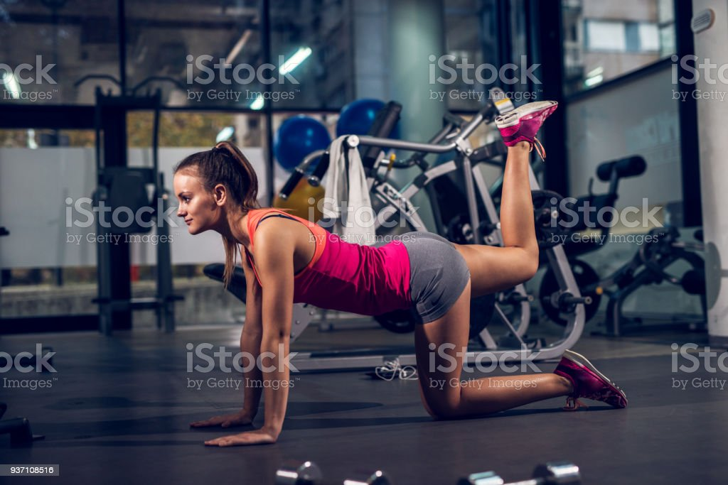 Side view of young focused satisfied attractive healthy sporty active shape girl doing legs exercises and warming while kneeling on the floor and raising one leg up in the gym. stock photo