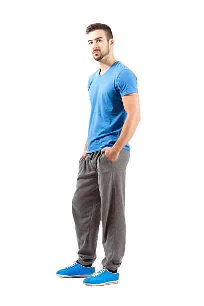 seitenansicht des jungen mann in sportbekleidung.  hände in den taschen - sweatpants stock-fotos und bilder
