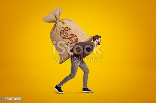 istock Side view of young handsome man in casual clothes carrying huge heavy sack with dollar symbol on. 1179973957