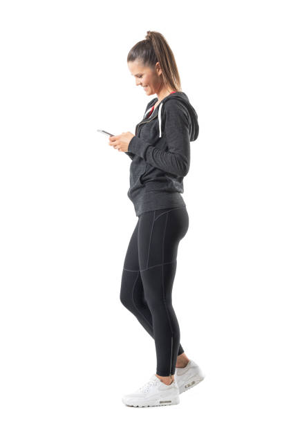 Side view of young happy fit runner woman using mobile phone and smiling stock photo