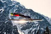 Side View of Young Male Ski Jumper in Mid-Air, Sun Reflection