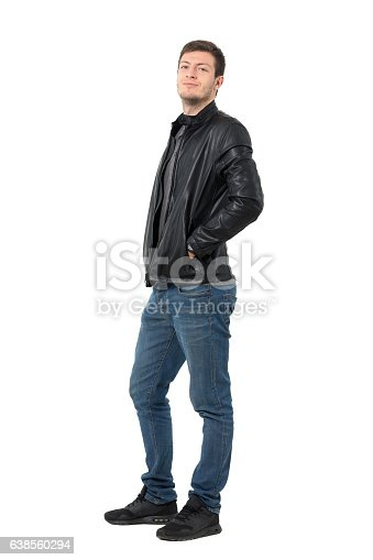 834639402istockphoto Side view of young man in jeans and jacket smirking 638560294