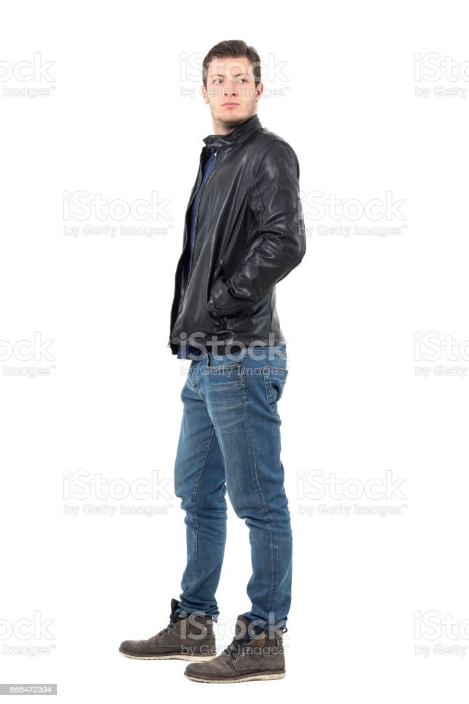 Side View Of Young Man In Leather Jacket And Jeans Looking Back Over