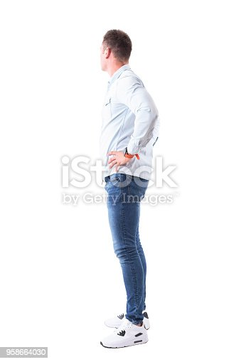 931173966istockphoto Side view of young man in light blue shirt and jeans with hands on hips looking behind 958664030