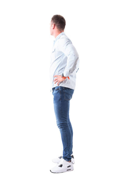 Side view of young man in light blue shirt and jeans with hands on hips looking behind Side view of young man in light blue shirt and jeans with hands on hips looking behind. Full body isolated on white background. akimbo stock pictures, royalty-free photos & images