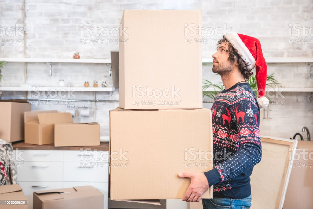 side view of young man in santa hat holding cardboard boxes during...