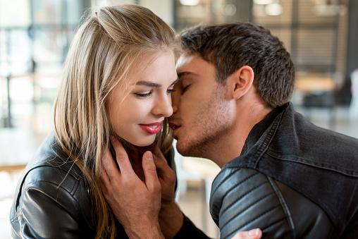 Side View Of Young Man Kissing Beautiful Girlfriend Stock