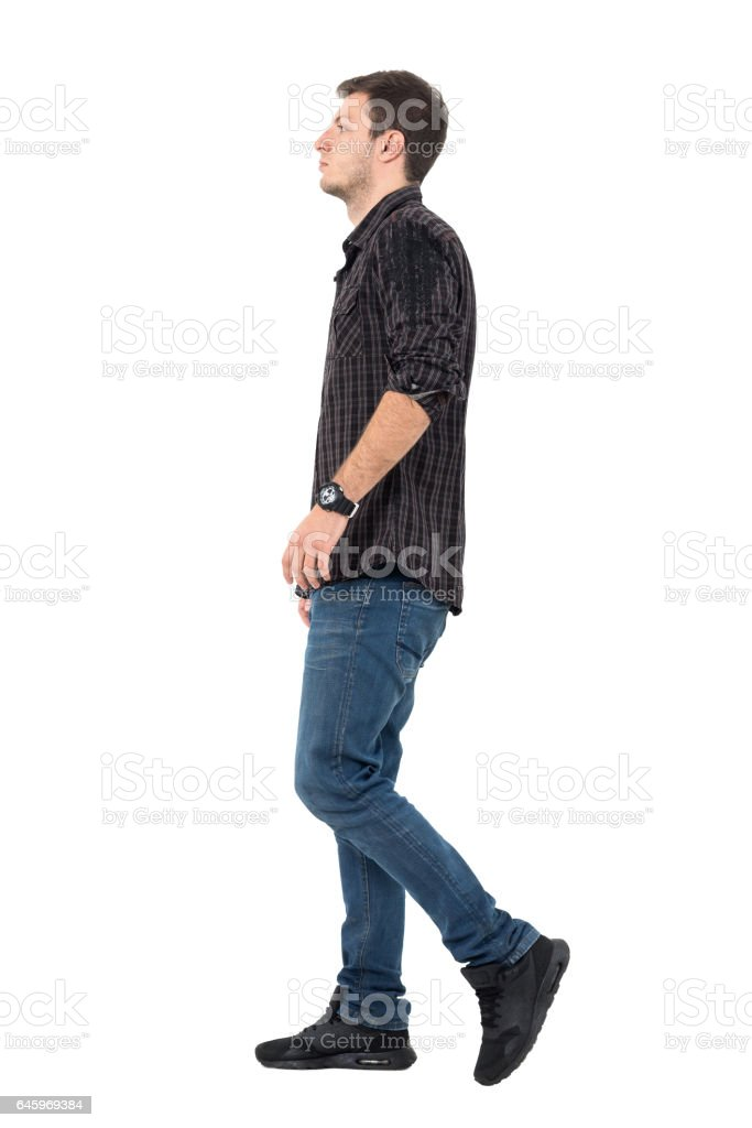 Side view of young man wearing jeans and shirt walking stock photo