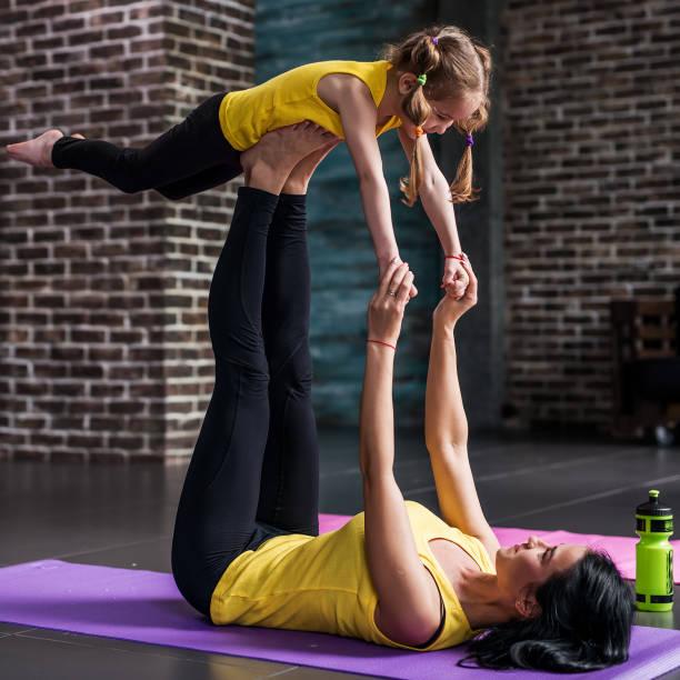 Vue latérale de la jeune mère et sa fille de faire des exercices à pratiquer l'yoga ensemble à la maison - Photo