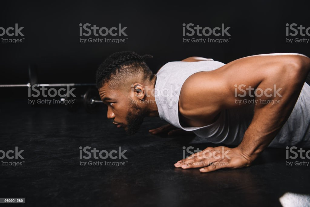 side view of young muscular african american man doing push-ups and looking away stock photo