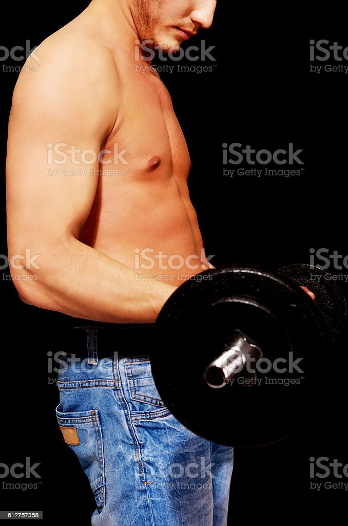 Side view of young muscular man weightlifting stock photo