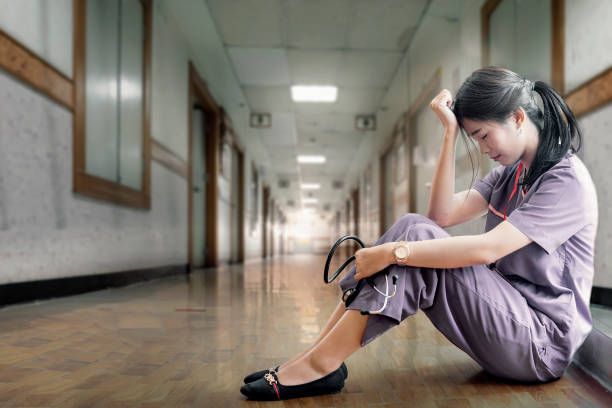 Vista lateral de la joven enfermera sentada en el suelo en el hospital. - foto de stock