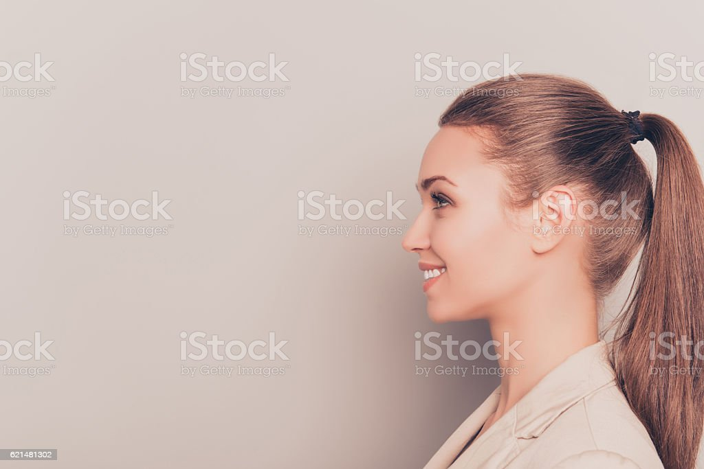 Side view of young smiling businesswoman isolated on gray background stock photo