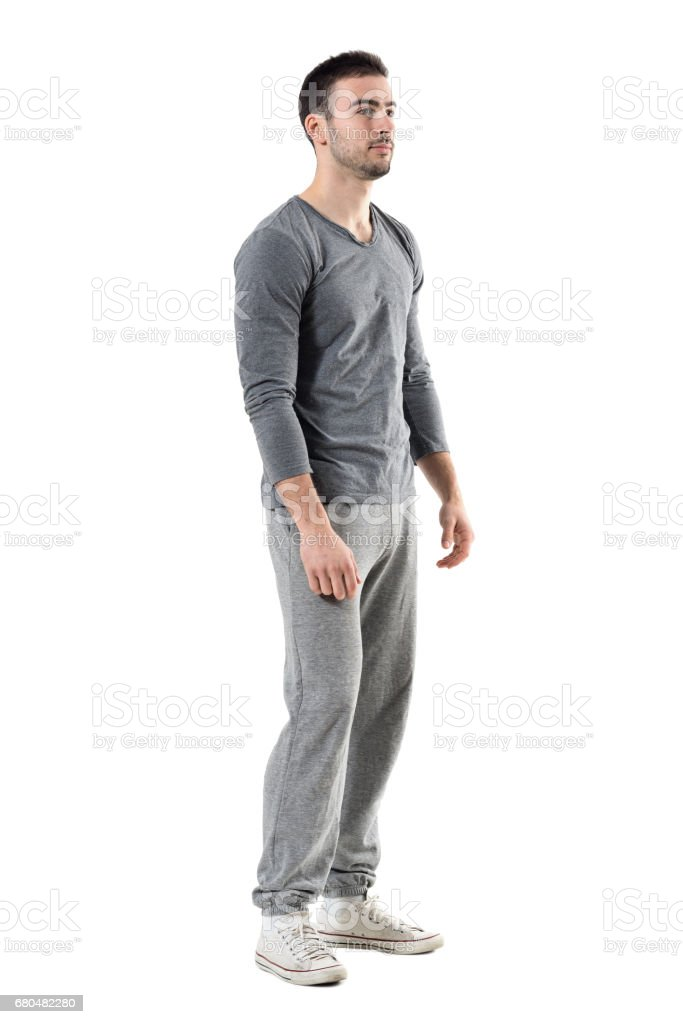 Side view of young sporty athletic man in sweatpants and sweatshirt looking away stock photo