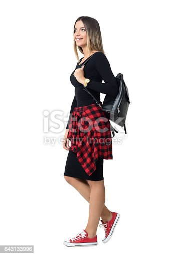 istock Side view of young student fashionable girl carrying bag walking 643133996