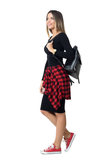 side view of young student fashionable girl carrying bag walking - waist bag stock photos and pictures