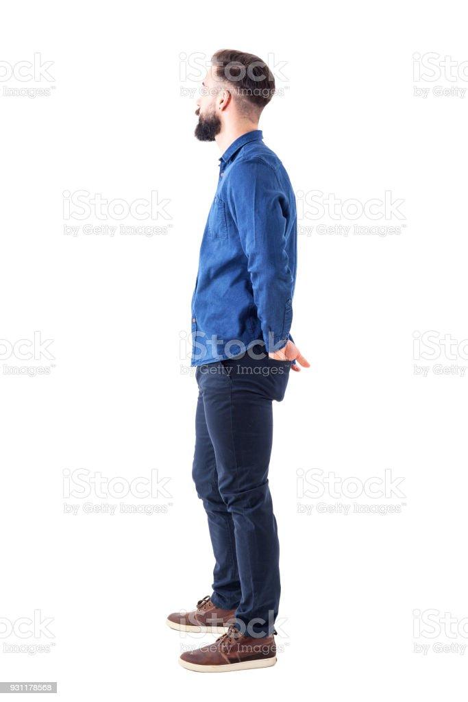両手後ろに若いスタイリッシュなひげを生やした男の側面ポケットに立って、見て ロイヤリティフリーストックフォト