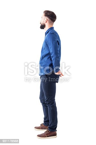 Side view of young stylish bearded man with hands in back pockets standing and watching. Full body isolated on white background.