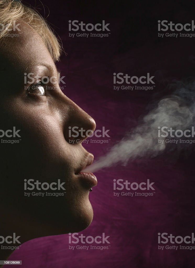 Side View of Young Woman Blowing Cigarette Smoke royalty-free stock photo