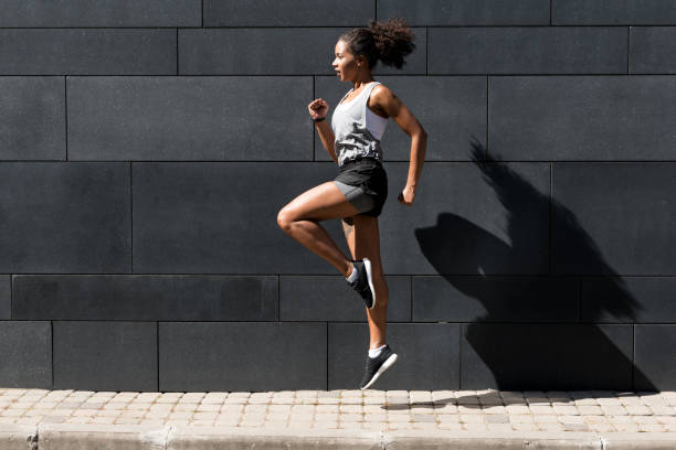 Side view of young woman doing exercising outdoors stock photo