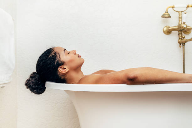Side view of young woman having a bath Side view of young woman having a bath bathtub stock pictures, royalty-free photos & images
