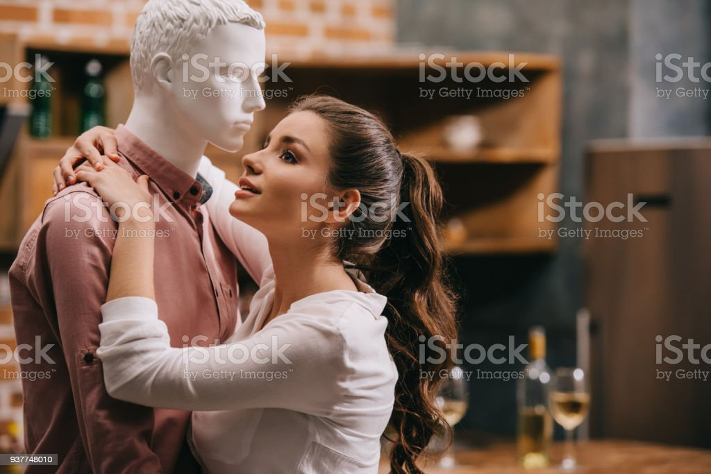 side view of young woman hugging layman doll at home, one way love...