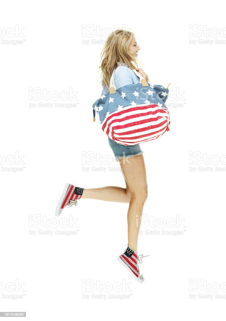 Side view of young woman jumping stock photo