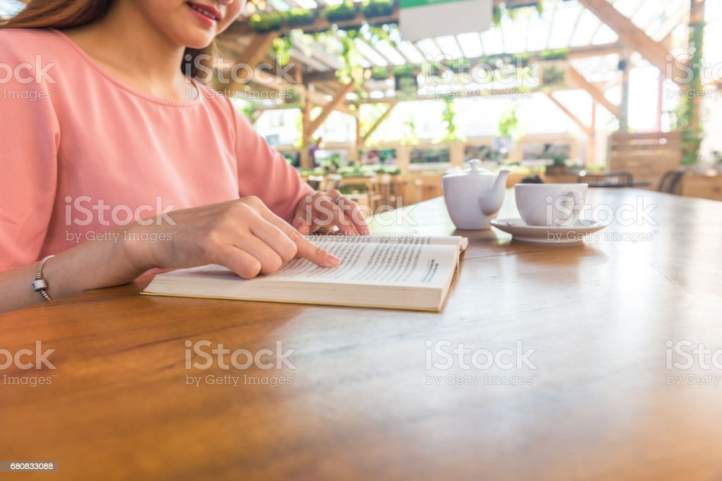 Side view of young woman reading book, having hot tea in the garden stock photo